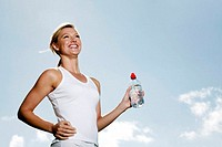 Woman holding a bottled water while jogging
