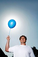 Man smiling while holding a blue balloon