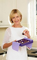 Senior woman holding a box of chocolates