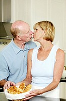 Senior couple kissing in the kitchen (thumbnail)