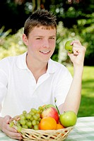 Boy smiling at the camera while holding a green apple