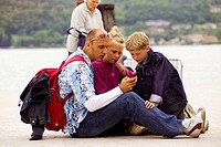 Italy, Lake Garda, father, children, shores, sitting, cell phone