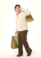 Side view of a young man carrying shopping bags.