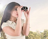 Arab tourist looking through binoculars at Dubai landmarks
