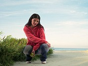 Woman with apple on the beach in Jebel Danah, Abu Dhabi, UAE (thumbnail)