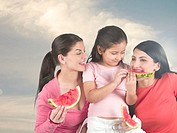 Women and child eating water melon slices
