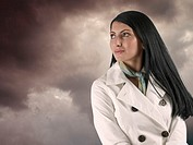 Woman wearing a coat looking at dark clouds in the sky