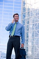 Businessman on cell phone by office building