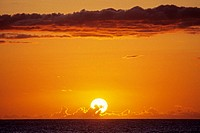 Hawaii, Sunball sinking into the dark ocean on the cloudy horizon