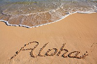 aloha written in the sand of a Hawaiian beach