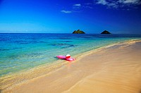 Hawaii, Oahu, Lanikai, Pink inflated raft and beachball on clear ocean water, Mokulua's in background