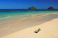 Hawaii, Oahu, Lanikai, Snorkel and mask rest on sandy tropical beach, Mokulua's in background