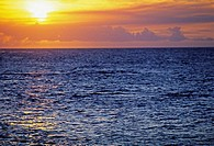 Cloudy orange and yellow sunset sky over blue ocean