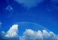 Hawaii, Rainbow arching over clouds in blue sky