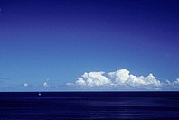 Puffy white clouds in blue sky over ocean