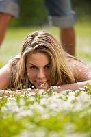 Young woman lying in meadow, young man in background