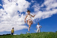 Girl (7-9) jumping in meadow, parents in background