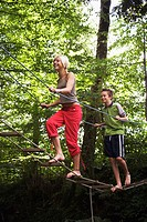 Teenage girl and boy walking on rope bridge, low angle view