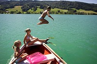 Girls (8-15) sitting on boat, one jumping in water, side view