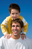 Boy (4-7) sitting on father's shoulders, portrait, close-up