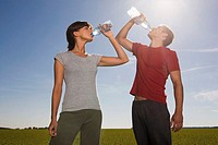 Young couple drinking from water bottle