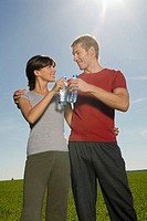 Young couple toasting with water bottle, smiling
