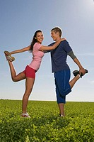 Young couple exerting gymnastic on meadow, side view