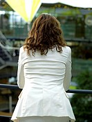 Businesswomn leaning on handrail, rear view