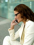 Businesswoman using mobile phone, close-up, side view