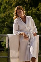 Woman wearing bath robe, leaning on railing