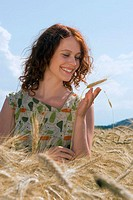 Young woman in cornfield, looking at cornstalk, smiling, close-up