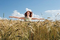 Young woman standing in cornfield, smiling, arms outstretched