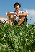 Young man sitting in meadow