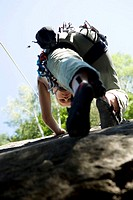 Young woman mountain climbing in climbing wall