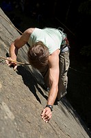 Young man mountain climbing in climbing wall