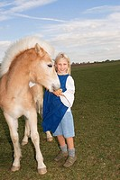 Girl (7-9) with pony on meadow, portrait