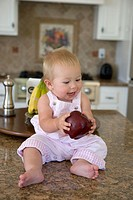 Blonde infant girl holding an apple