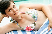 Young woman in bikini lounging by pool