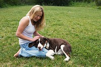 Smiling blonde teen girl in blue jeans and white tank top kneeling on grass lawn, pets her dog´s head resting on her leg.
