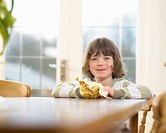 Girl (5-7) with easter egg at table, smiling, portrait