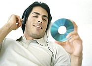 Man listening to headphones, looking at CD
