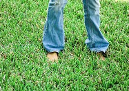 Person in jeans standing in grass, low section