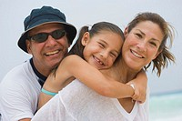 Parents with daughter (5-6) on beach, smiling, portrait
