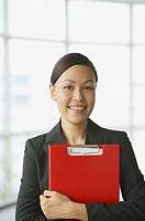 Businesswoman carrying file, smiling at camera