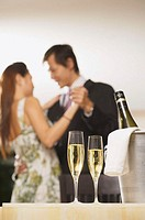 Champagne glasses and bottle in foreground, couple dancing in background