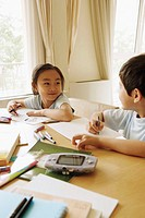 Children at home, sitting on table with drawing materials