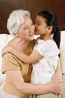 Granddaughter kissing grandmother, portrait