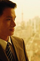 Businessman standing next to window, buildings in the background