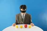 Businessman blindfolded, sitting in front of three lemons and an apple