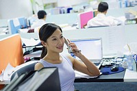 Executives in office, woman in cubicle using telephone
